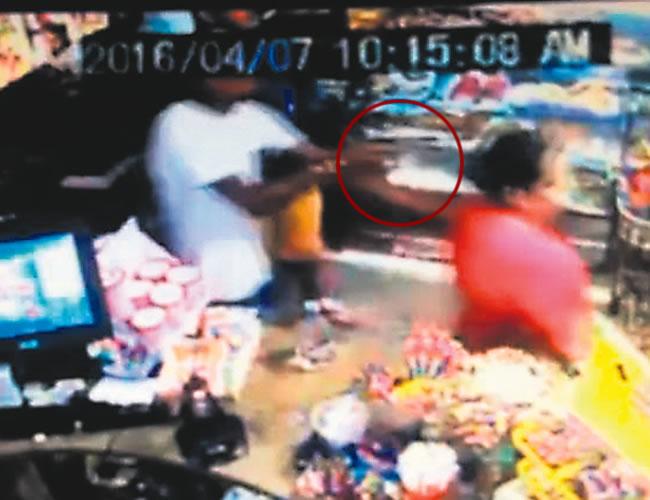 Momento en que uno de los ladrones le apunta al administrador de la licorería | Foto: Captura de pantalla