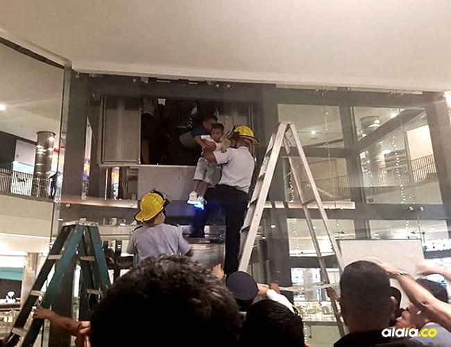 Un menor es sacado del ascensor por uno de los bomberos. | El Heraldo