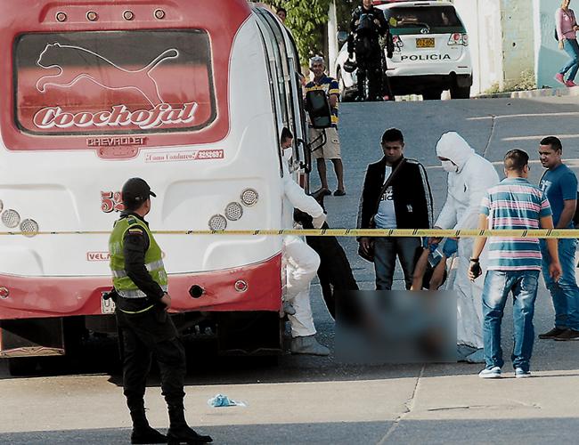 Instante en que miembros del CTI de la Fiscalía sacaban del bus de Coochofal el cuerpo sin vida del delincuente abatido, John Jairo Serrano Valdéz. | Foto: Al Día