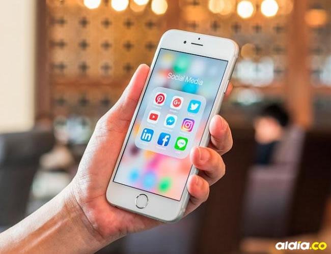 Persona sostiene un teléfono en su mano, en el que se ve la carpeta 'social media'. | Al Día