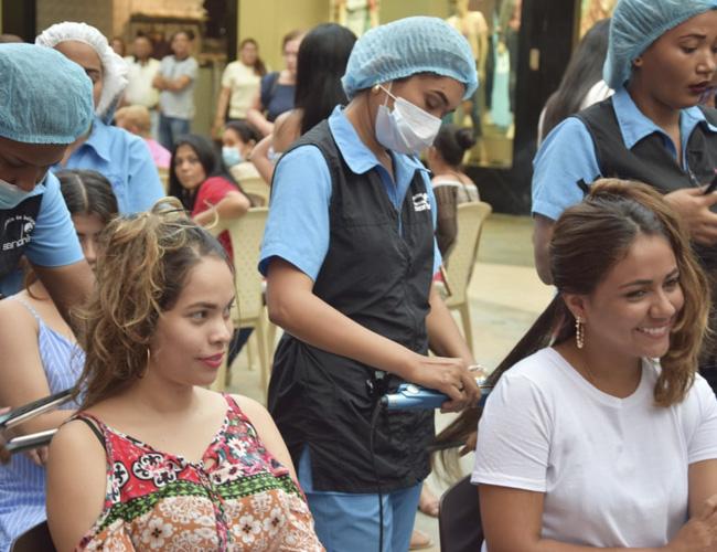 Profesionales en el corte de cabello son las encargadas de recibir las donaciones para esta campaña.
