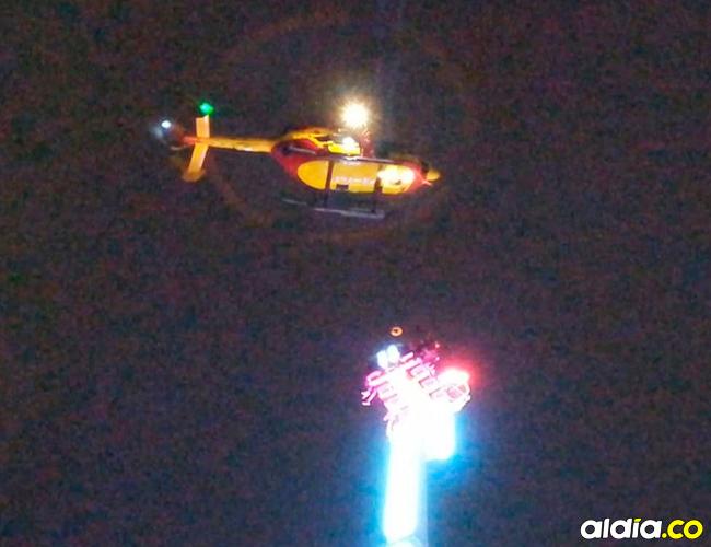 Momentos en que socorristas a bordo de en un helicóptero intentan rescatar a las personas atrapadas en la atracción mecánica. | AFP