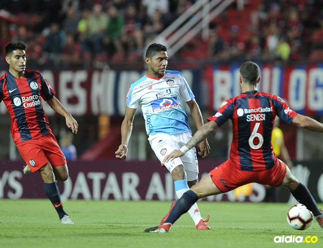 El delantero samario Luis Carlos Ruiz encara la marca de dos defensores de San Lorenzo.