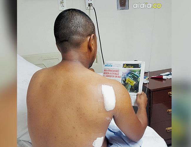 Daniel García, de 41 años, lee en AL DÍA la noticia de su atraco en la habitación de la clínica donde se recupera de las heridas que le causaron los atracadores.