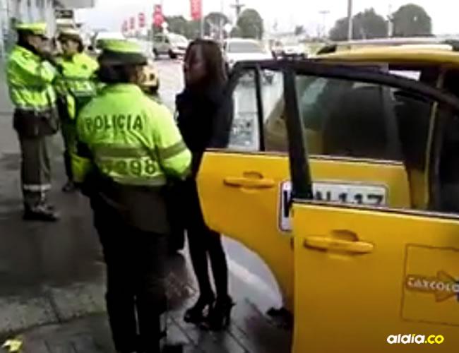 Una policía de tránsito ayudaba a la mujer invidente en el aeropuerto El Dorado | Captura