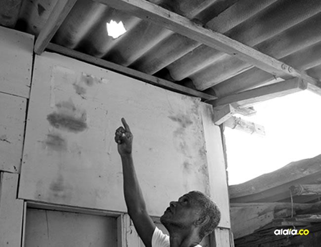 Daniel Briston, el chamán, sostiene un hilo negro para amarrar al supuesto duende. Al lado, un techo destrozado. EL HERALDO