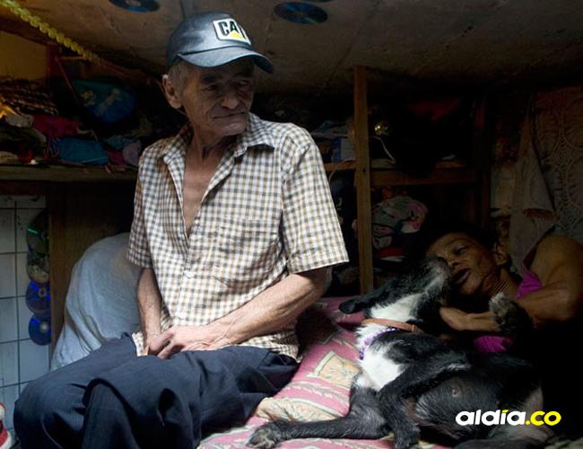 Miguel Restrepo su esposa y su perro, en una cama adentro de una alcantarilla en Medellín   AFP
