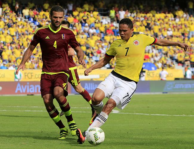 Bacca (der.) en un cruce de balón frente al defensor venezolano Oswaldo Vizcarrondo, en el triunfo 2-0 de Colombia.