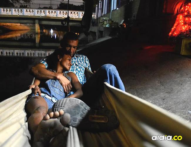 Orlando Salcedo y Elles Cabarcas se acurrucan en una hamaca debajo del puente ubicado frente a la Intendencia Fluvial. Un arbolito de Navidad los ilumina. | Christian Mercado
