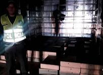 Un miembro de la Policía Nacional custodia las 101 cajas con monedas de 500 pesos | Cortesía