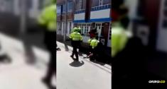 En medio de la trifulca, una mujer intenta intervenir para ayudar al hombre, pero uno de los policías la golpea dejándola inconsciente en el piso | Captura de pantalla