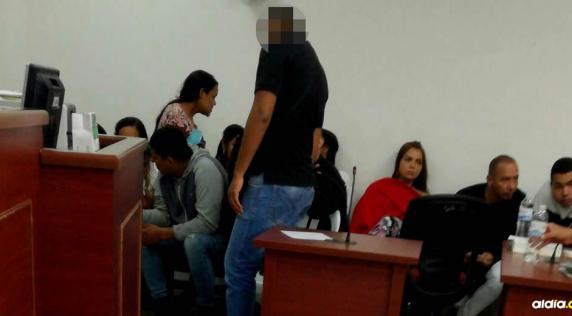 Un policía custodia a los capturados en la 'Operación Mercurio' durante una diligencia llevada a cabo esta semana en el Centro de Servicios Judiciales   Cortesía