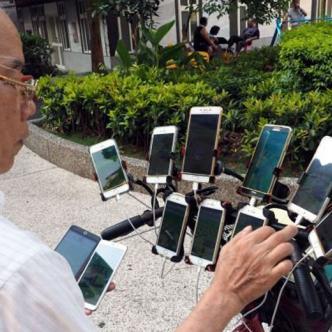 Hombre de 70 años en uno de sus recorridos con sus 11 celulares conectados a una bicicleta.
