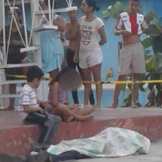 Los nietos de la víctima observan el cuerpo de su abuelo, asesinado de una puñalada en la espalda.   Cortesía