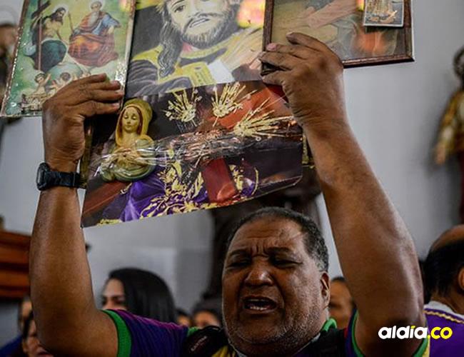 Un feligrés levanta imágenes religiosas este miércoles en la basílica de Santa Teresa, en el centro de Caracas   AFP