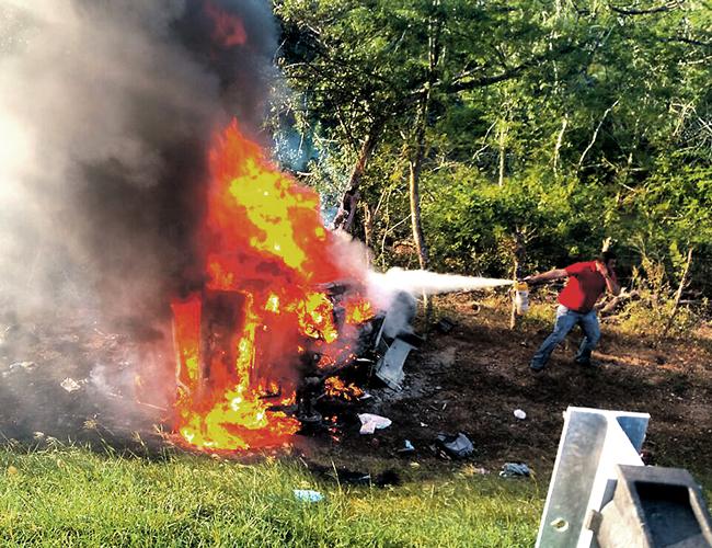 Un voluntario trata de apagar las llamas en la camioneta tipo van.   Foto: AL DÍA